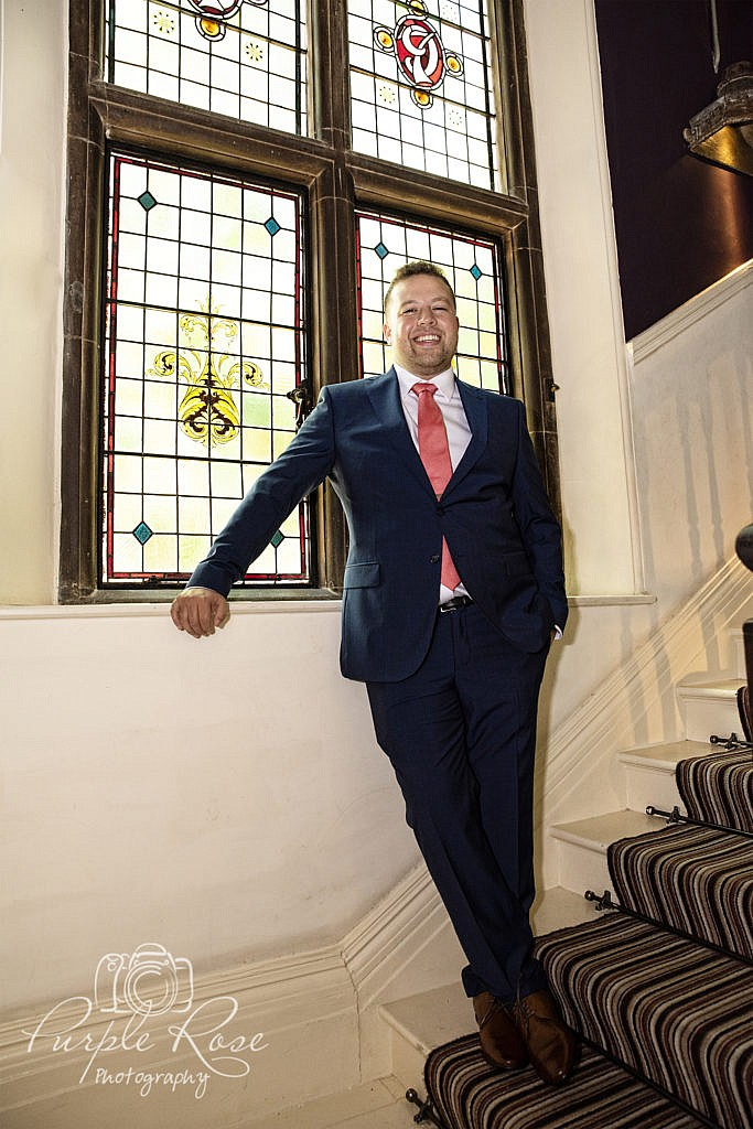 Groom leaning by a window