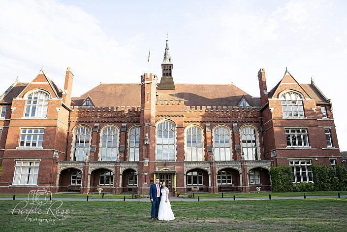 Bride & groom standing outside Bedford School