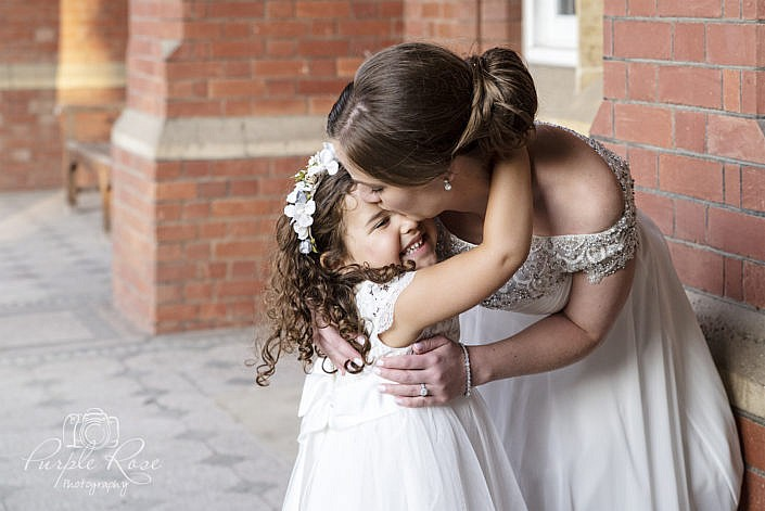 Bride embracing a flower girl