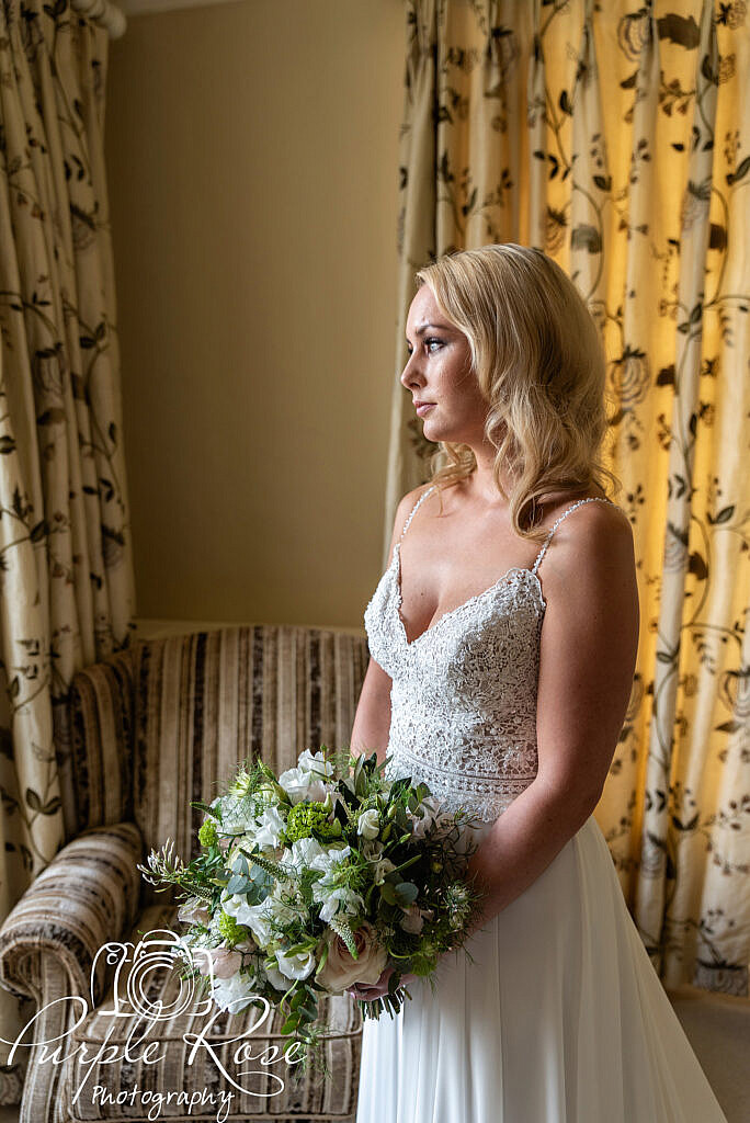 Bride holding her bouquet and looking out the iwndow