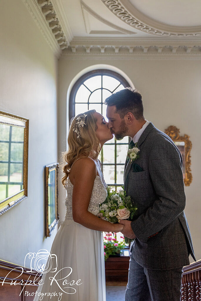 Bride and groom kissing in front of a window
