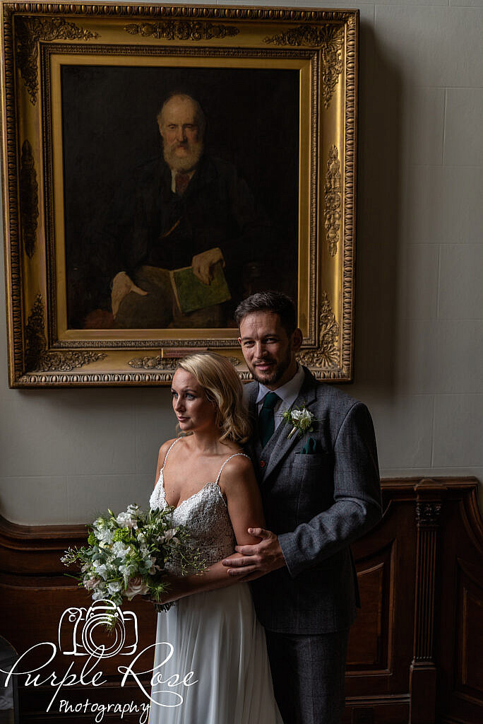 Bride and groom in front of an oil painting