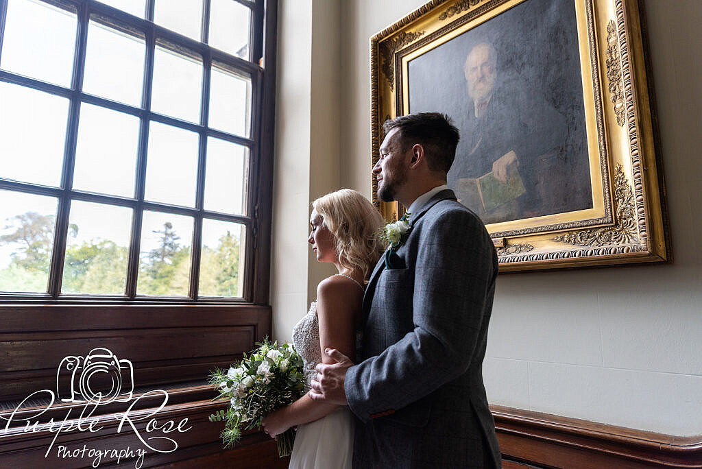 Bride and groom looking out a window