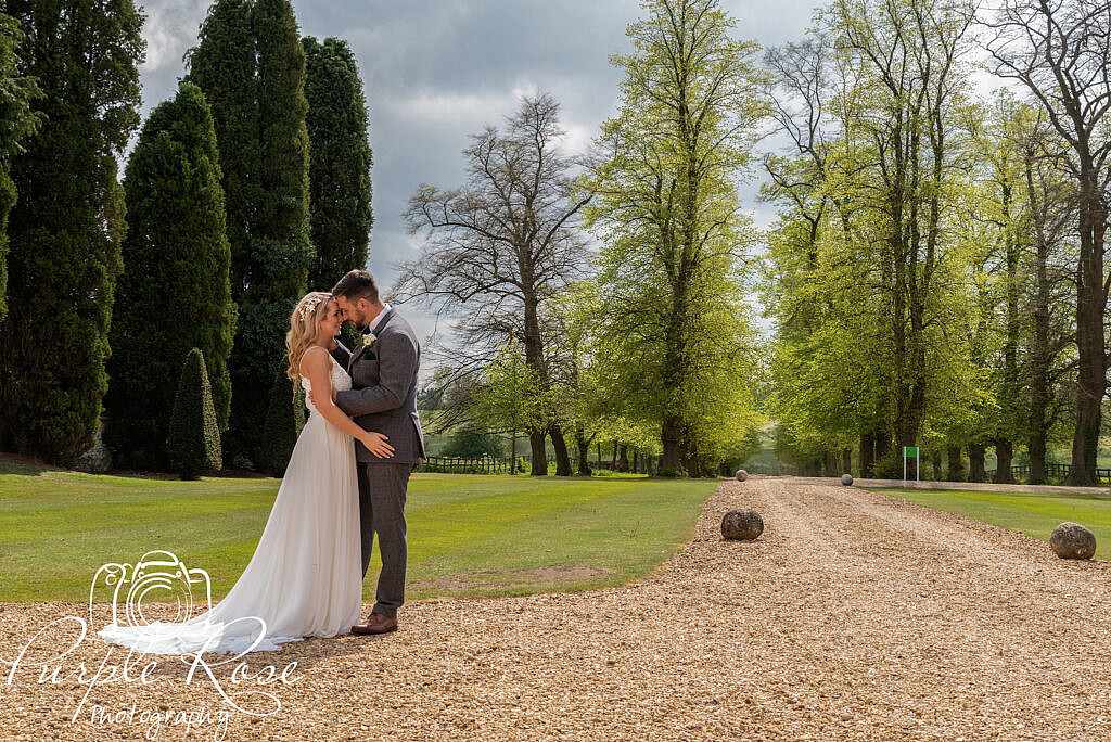Bride and groom standing on stone pathway