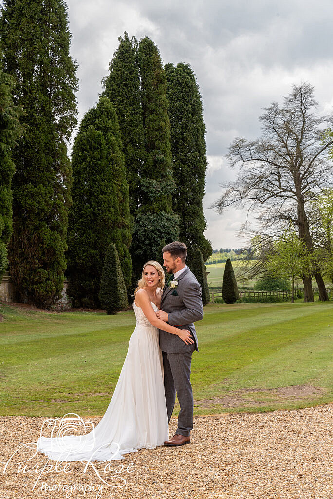 Bride and groom laughing in their venues gardens