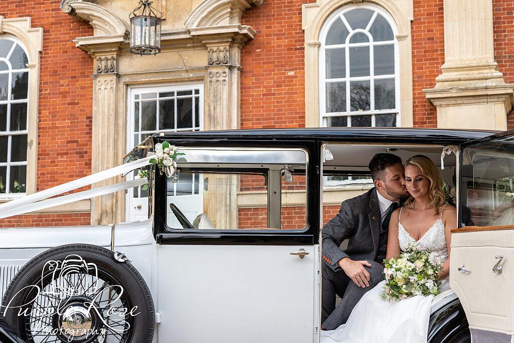 Bride and groom sat in their wedding car
