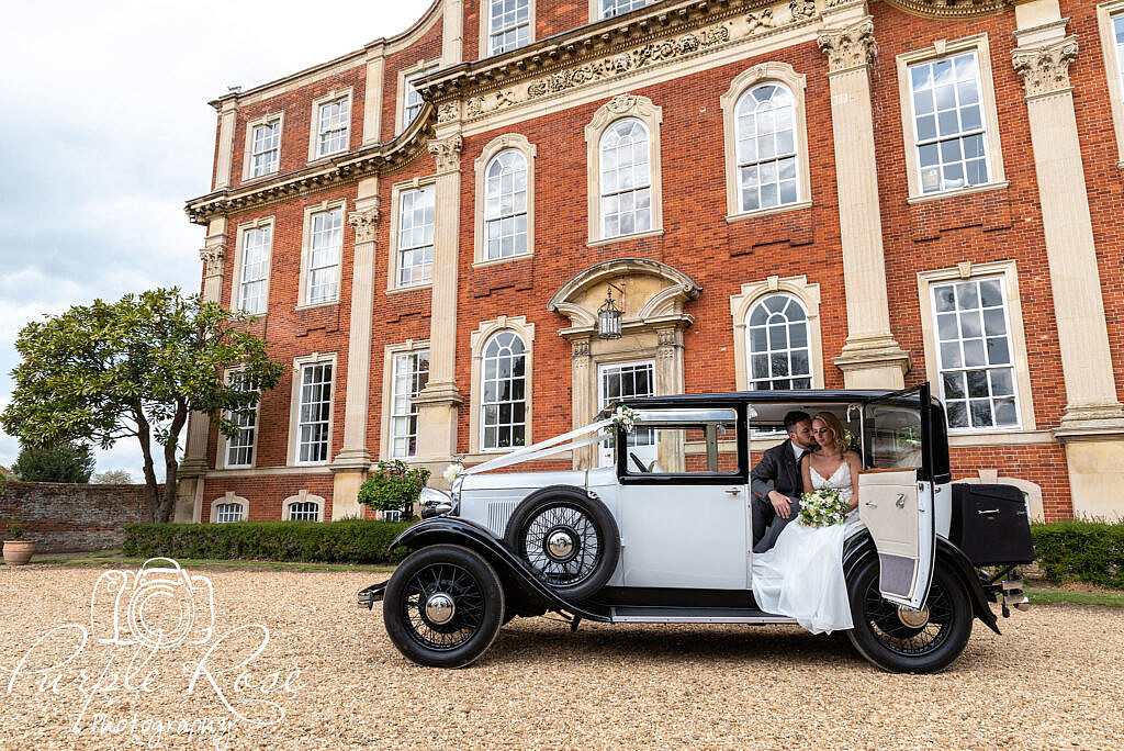 Bride and groom sat in their wedding car in front of their venue