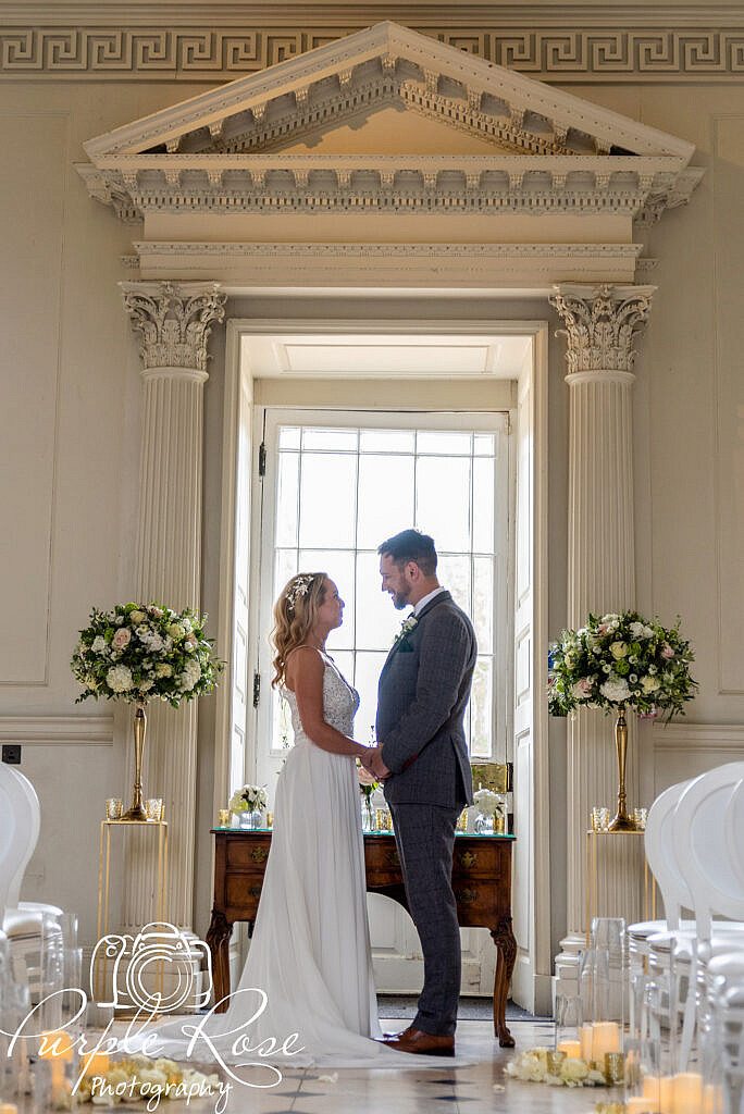 Bride and groom standing together in front of a large window
