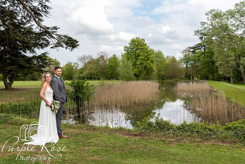Bride and groom standing by a lake