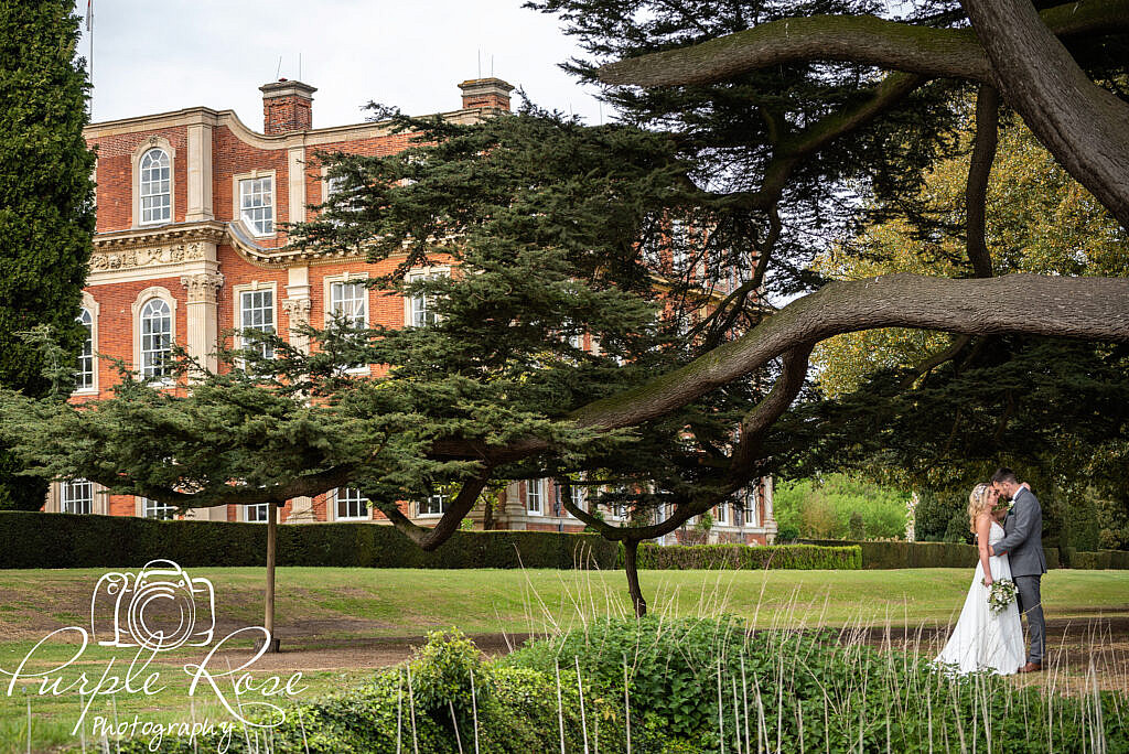 Bride and groom under a tree with Chicheley Hall in the background