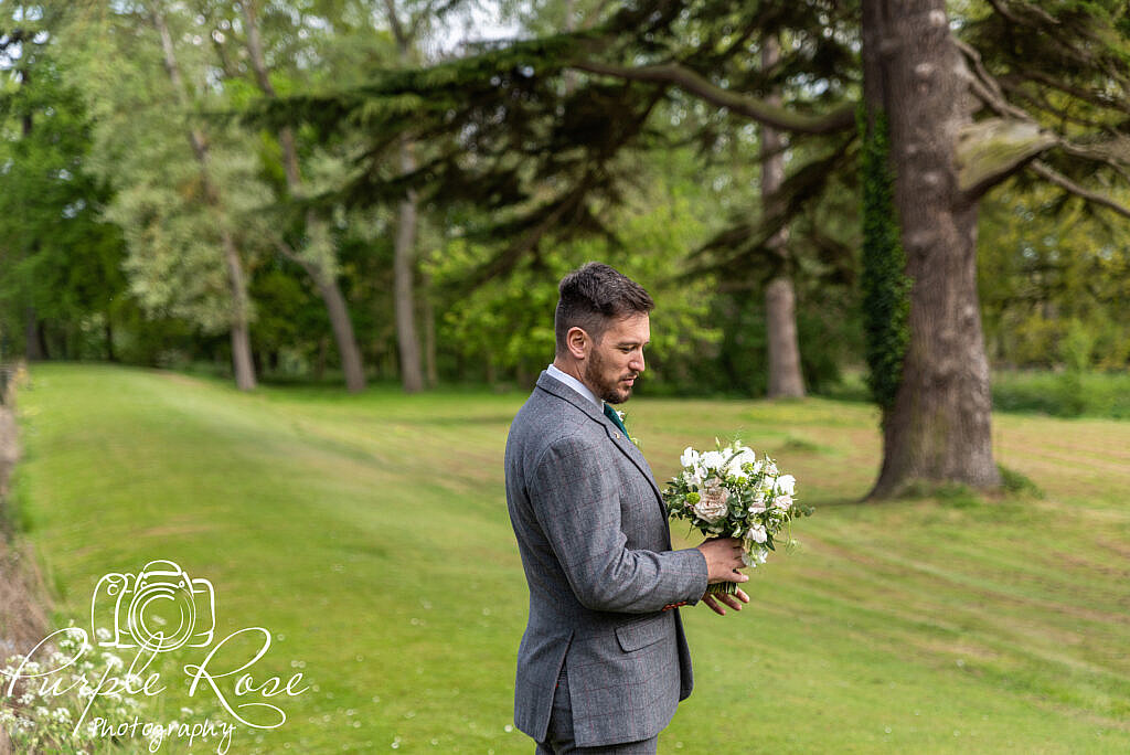 Groom holding the brides flowers