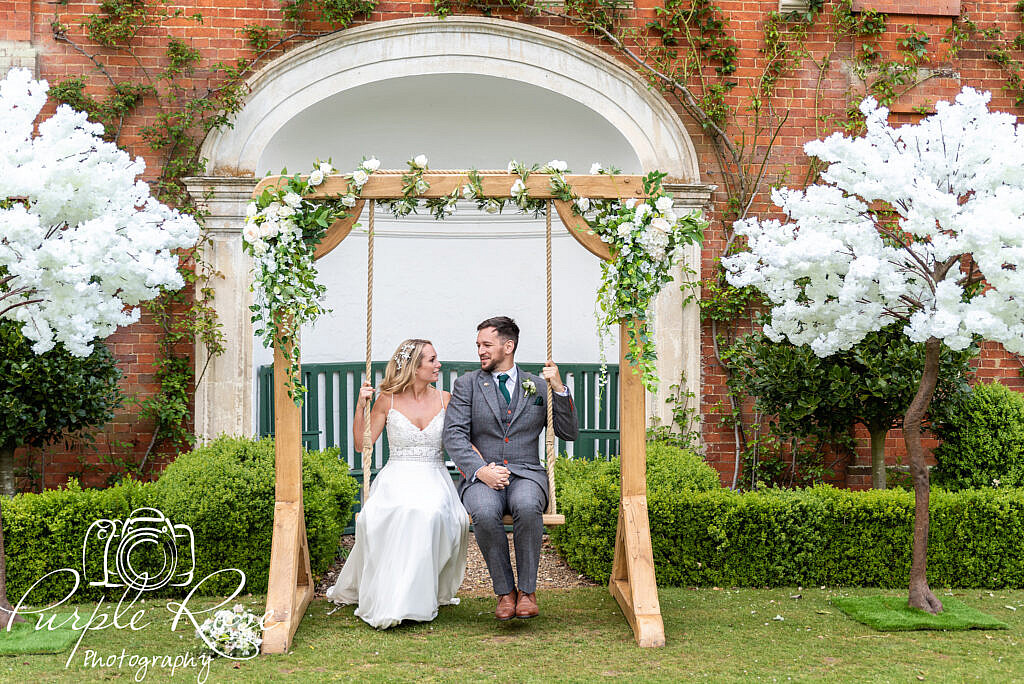 Bride and groom playing on a swing