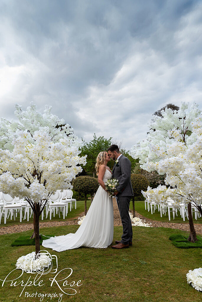 Bride and groom standing in wedding venues garden with a dramatic sky