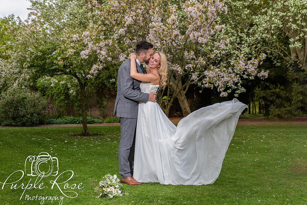 Bride and groom surrounded by cherry blossom trees