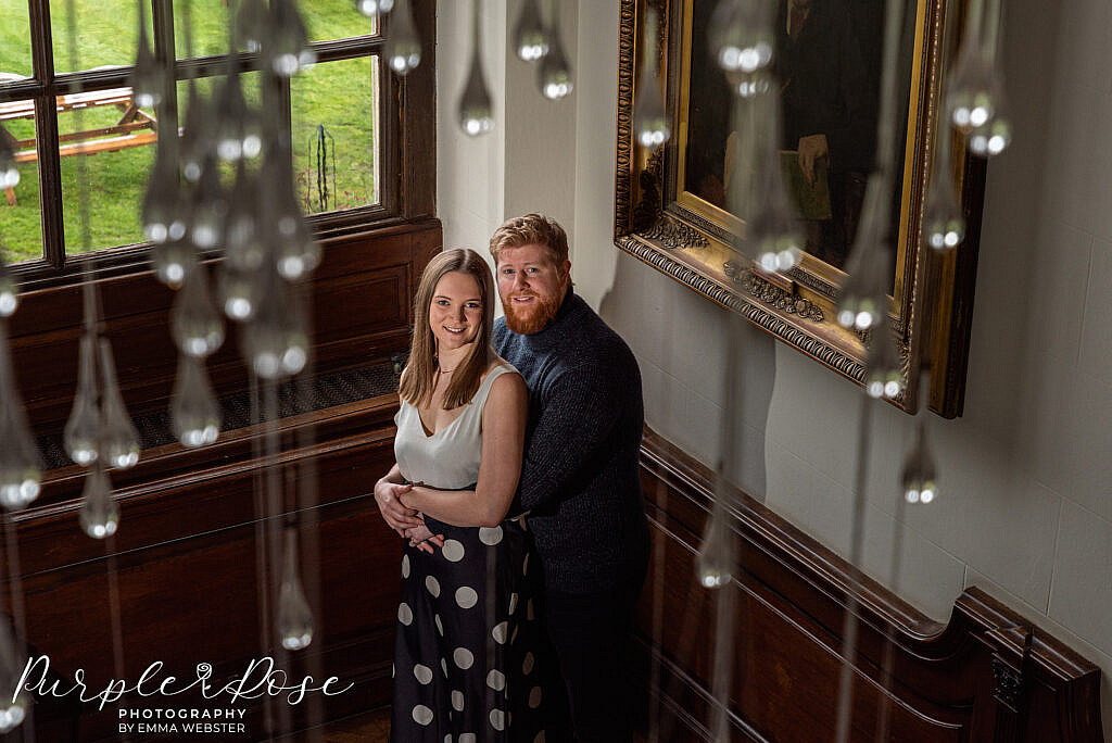 Couple standing by a window taken through a chandelier