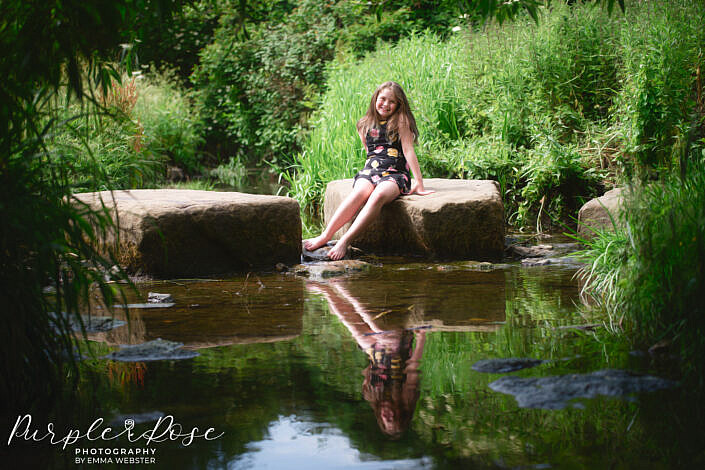 Girl sat on a rock in a stream