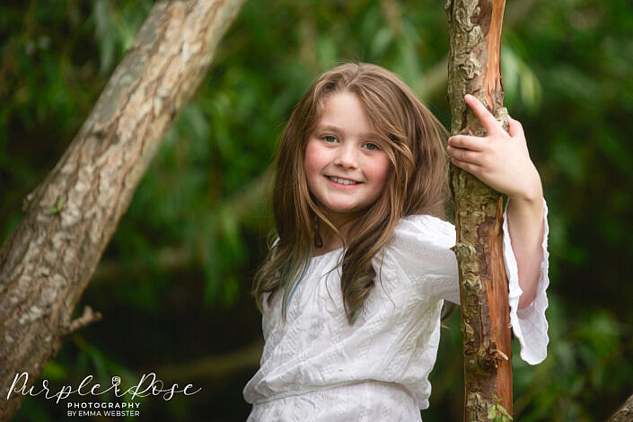 Girl leaning on a tree branch