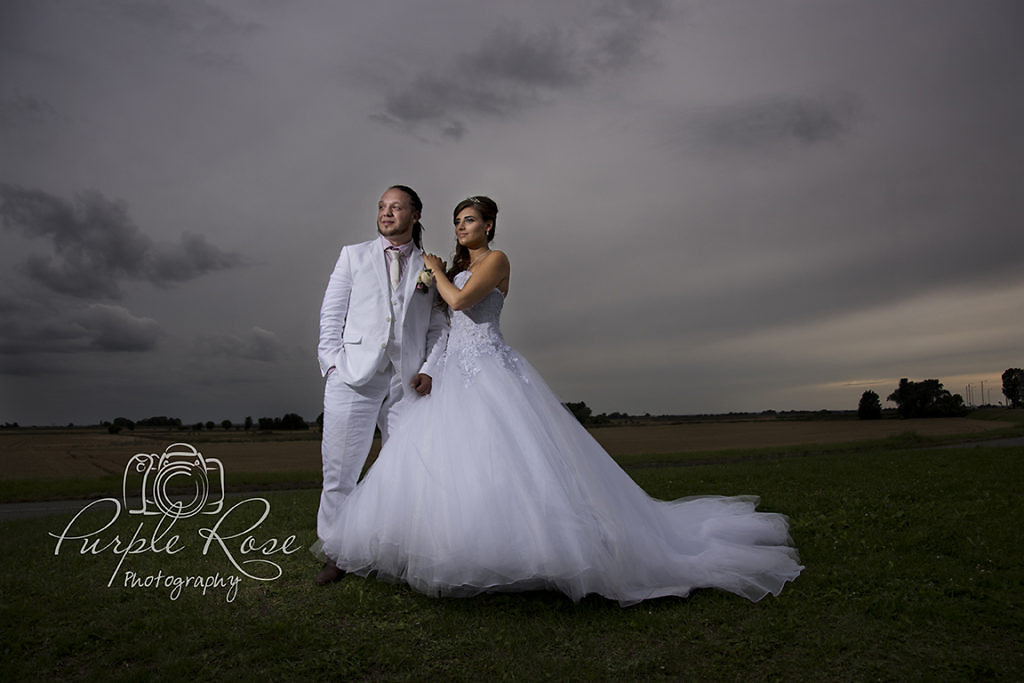 Bride and groom stood in front of a stormy sky