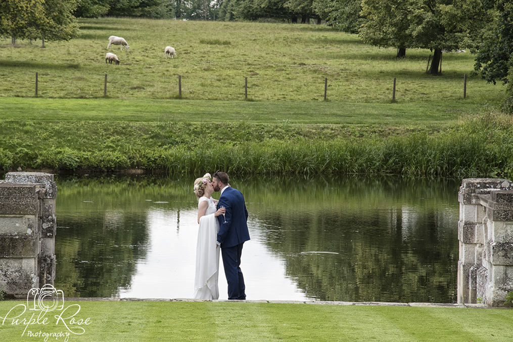 Bride and groom standing in front of a lake