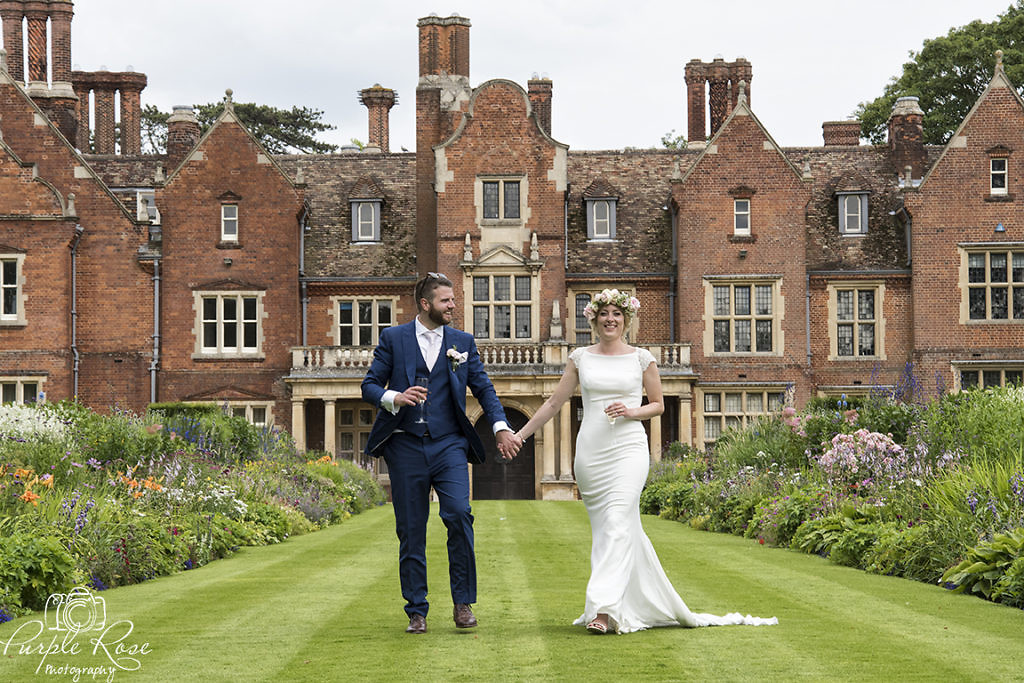 Bride and groom walking with Longstowe Hall behind them