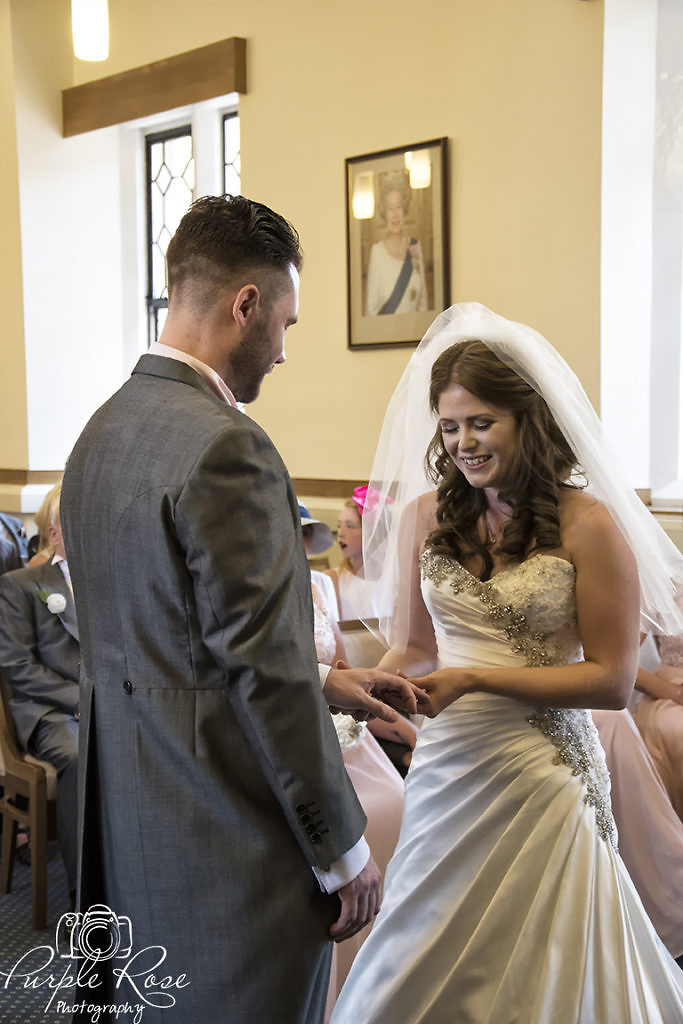 Bride and groom exchanging rings during their wedding ceremony