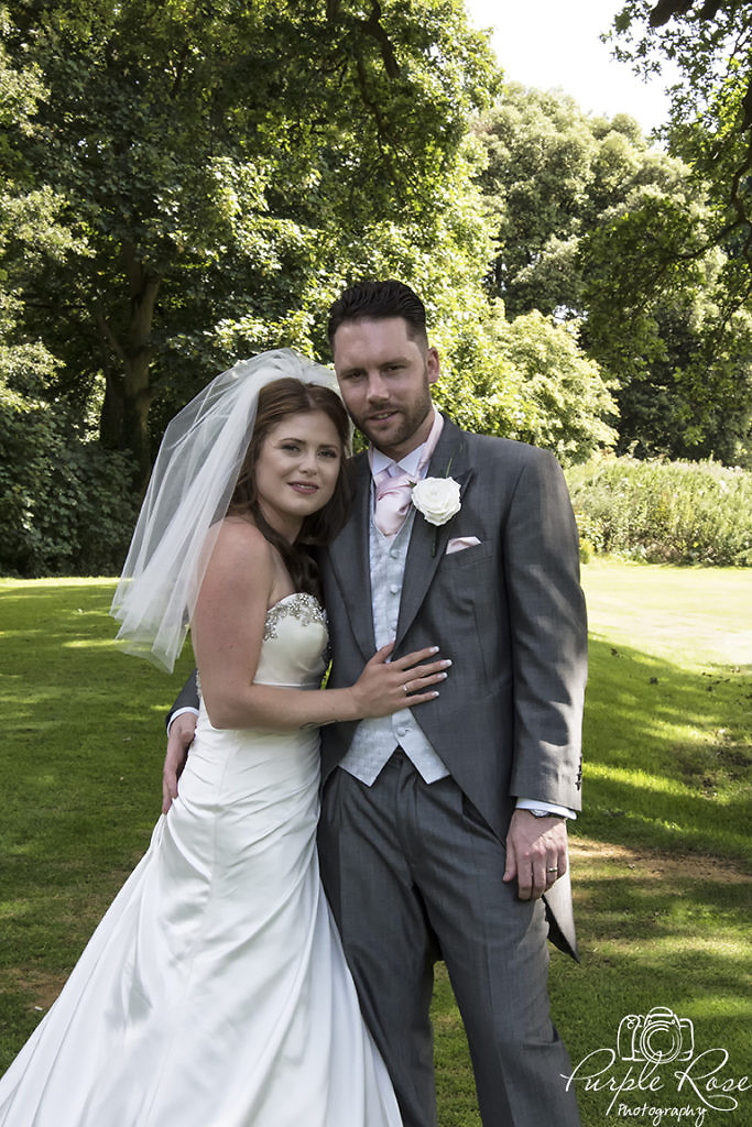 Bride and groom embracing in their venues garden