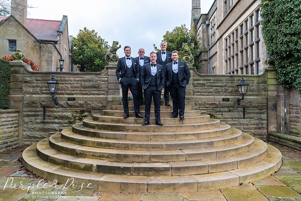 Groom and groomsmen on the steps at their venue