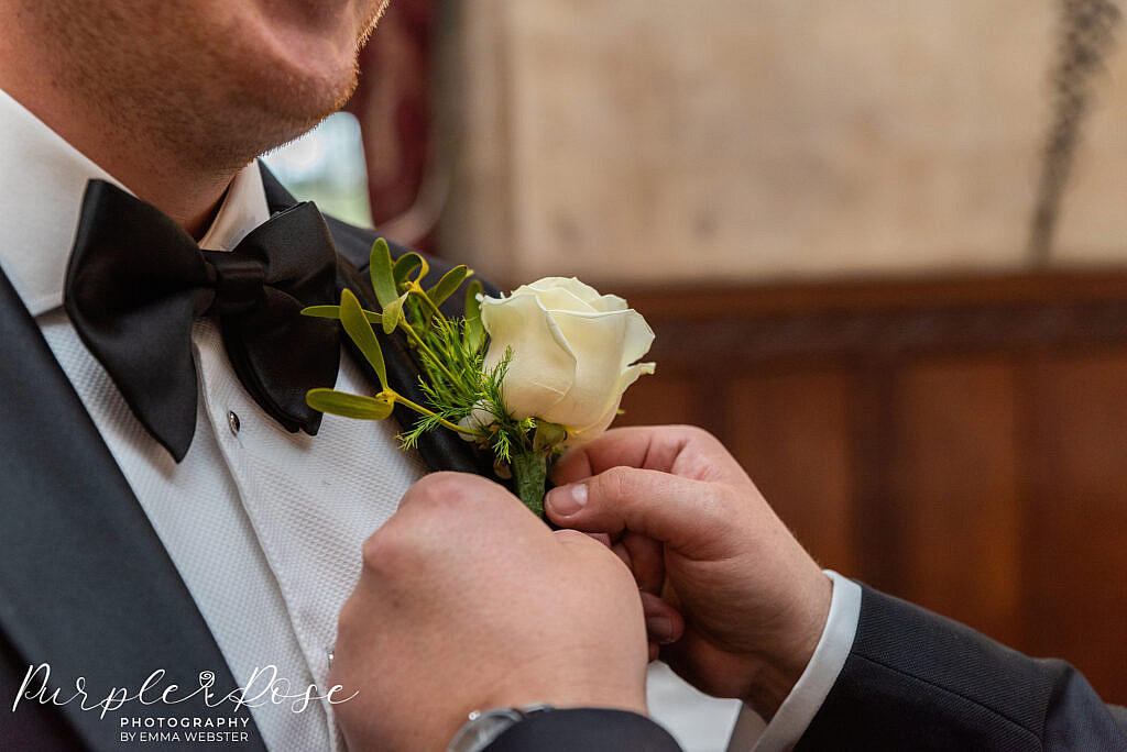 Grooms button hole being attached