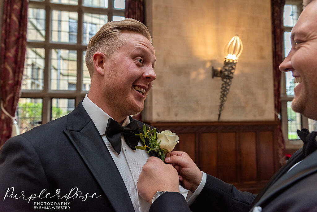 Groom laughing as hid buttonhole is attached