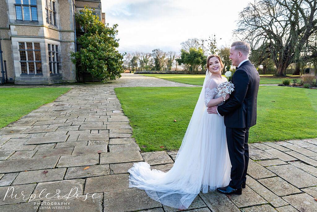 Bride and groom standing in gardens