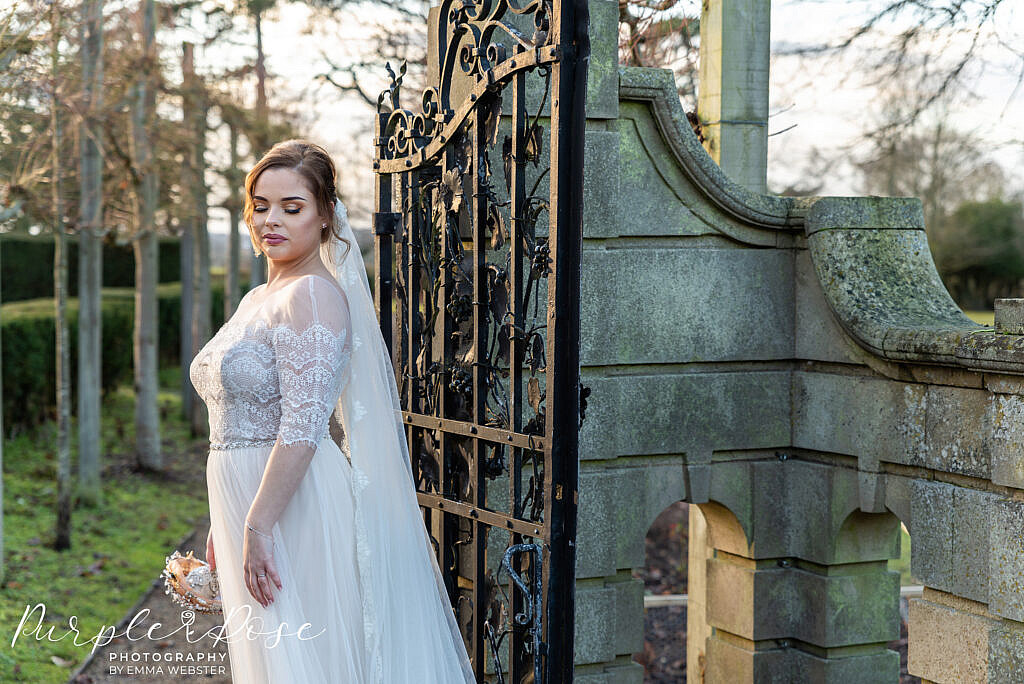 bride standing by a metal gate