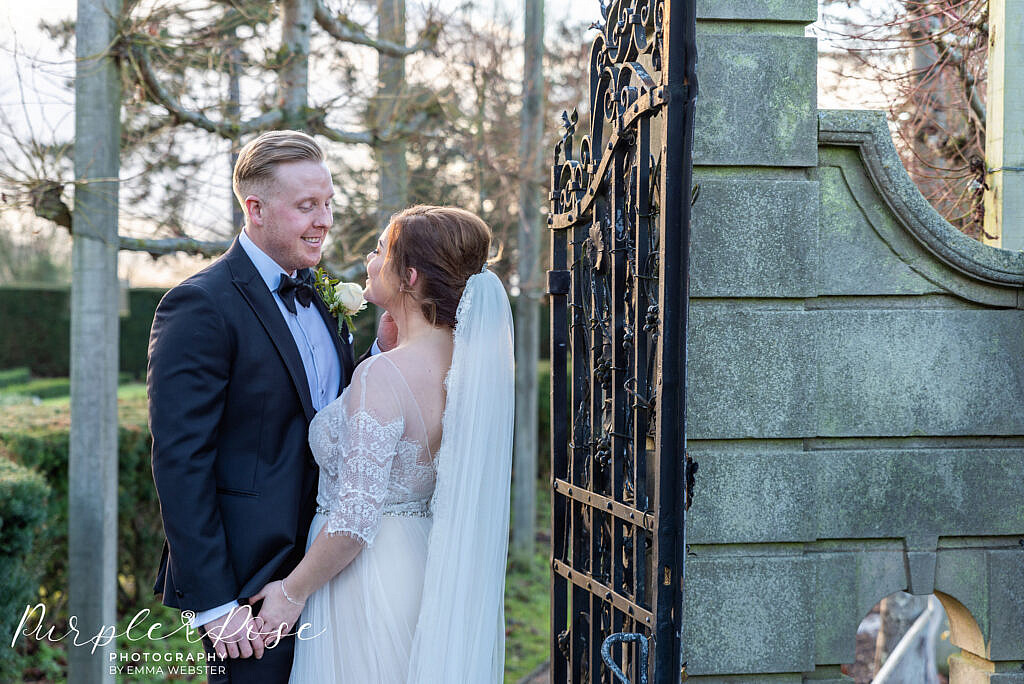 bride and groom standing by a metal gate