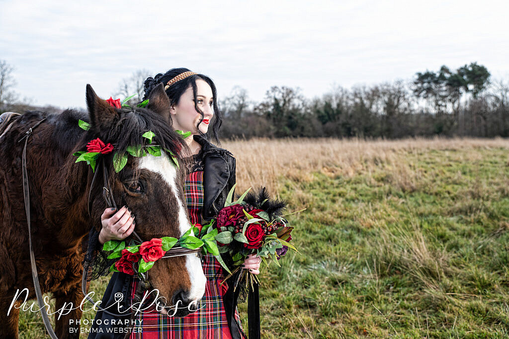 Bride in black and red with a horse