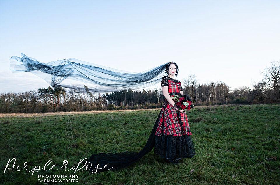 Gothic bride with black wedding veil flowing behind her