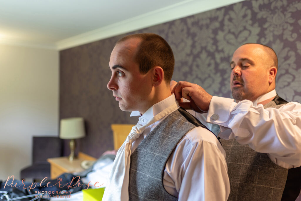 Best man helping groom adjust his collar