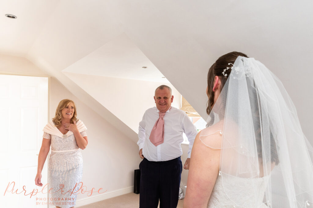 Parents seeing their daughter in her wedding dress