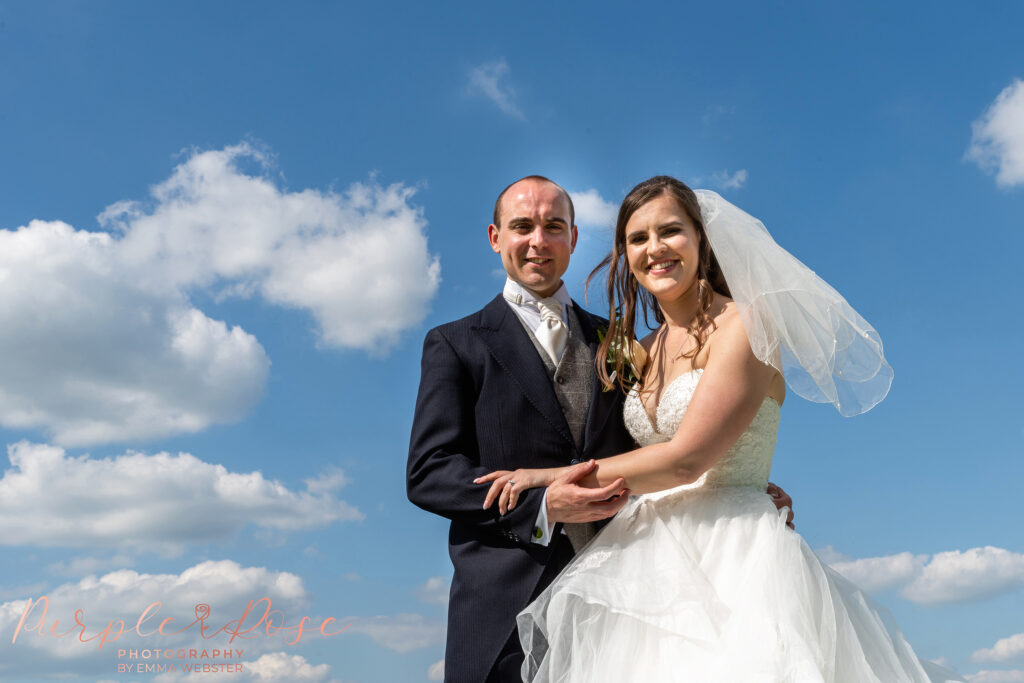 Bride and groom framed by blue sky and scattered clouds