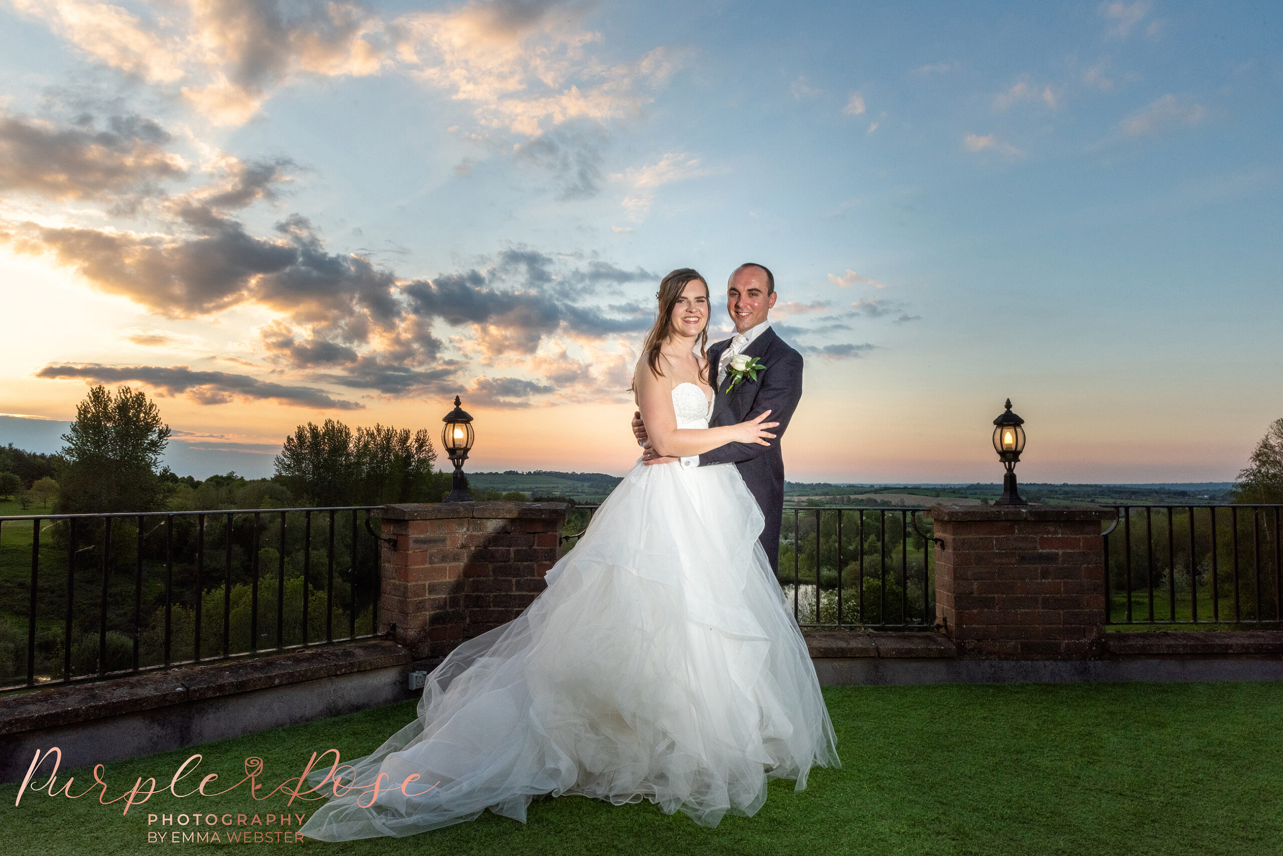 Bride and groom in front of a sunset on a balcony