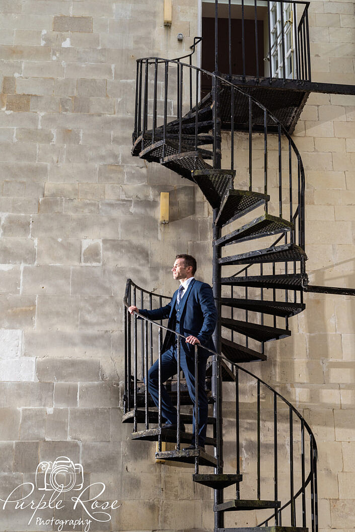 Groom standing on a spiral staircase