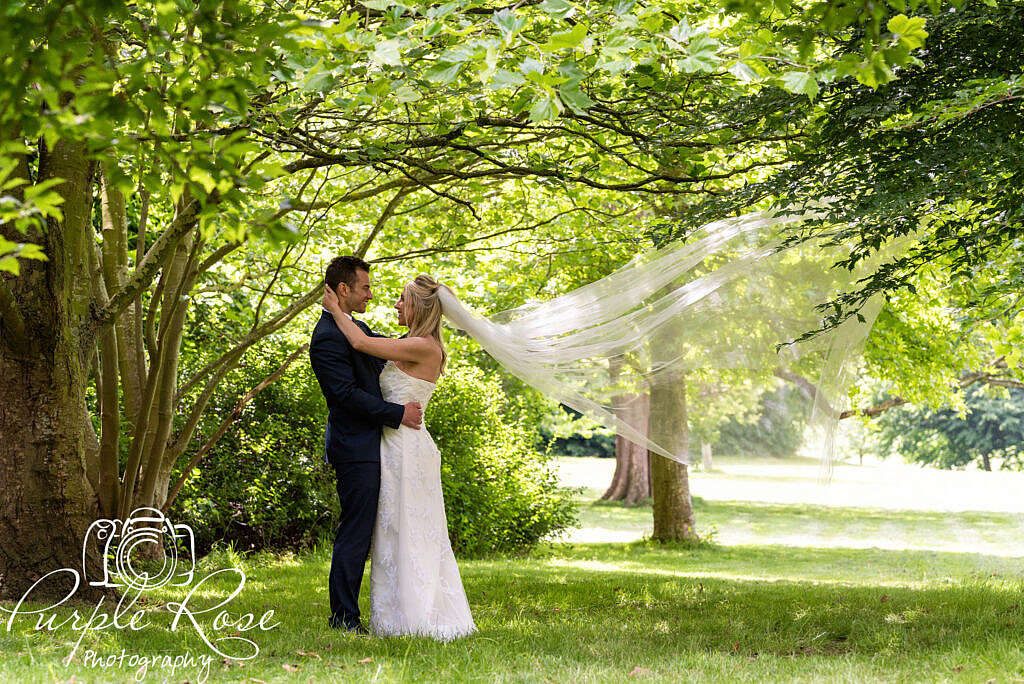 Bride and groom embracing in a forest
