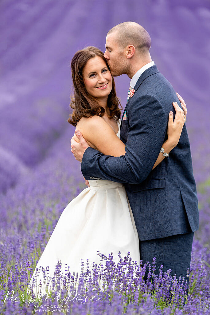 Bride being kissed by her groom in a lavender field