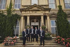 Groomsmen standing in front of wedding venue
