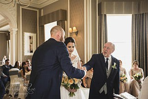 Groom shaking father of the brides hand