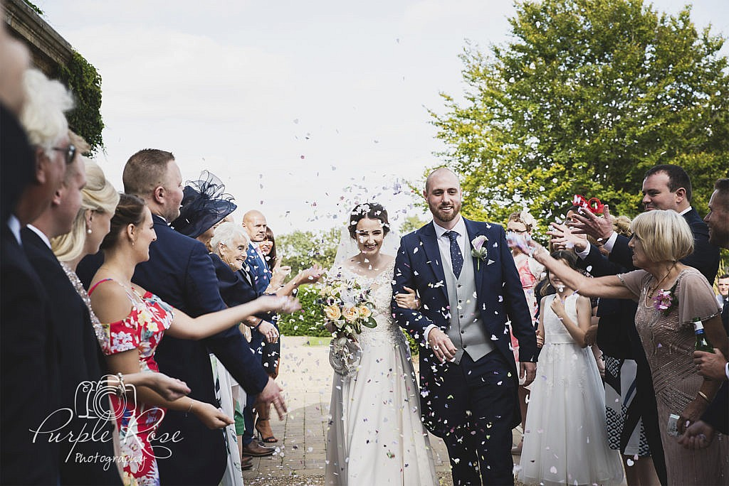 Bride and groom being congratulated by their guests