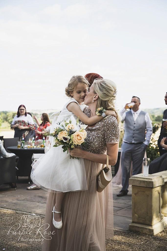Flower girl hugging her mum