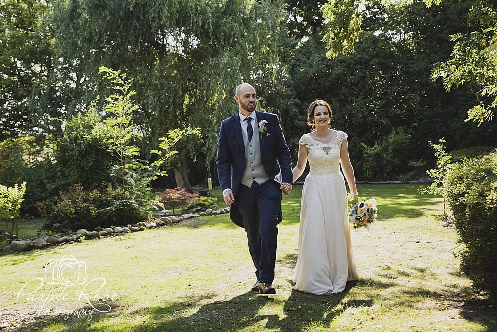 Bride and groom walking through a garden