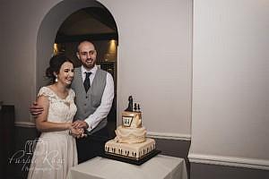 Bride and groom preparing to cut their wedding cake
