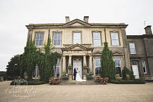 Bride and groom standing in front of their wedding venue