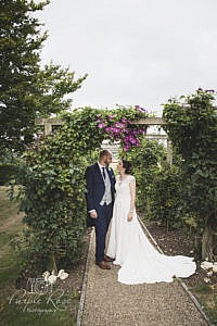 Bride and groom stood under a floral arch