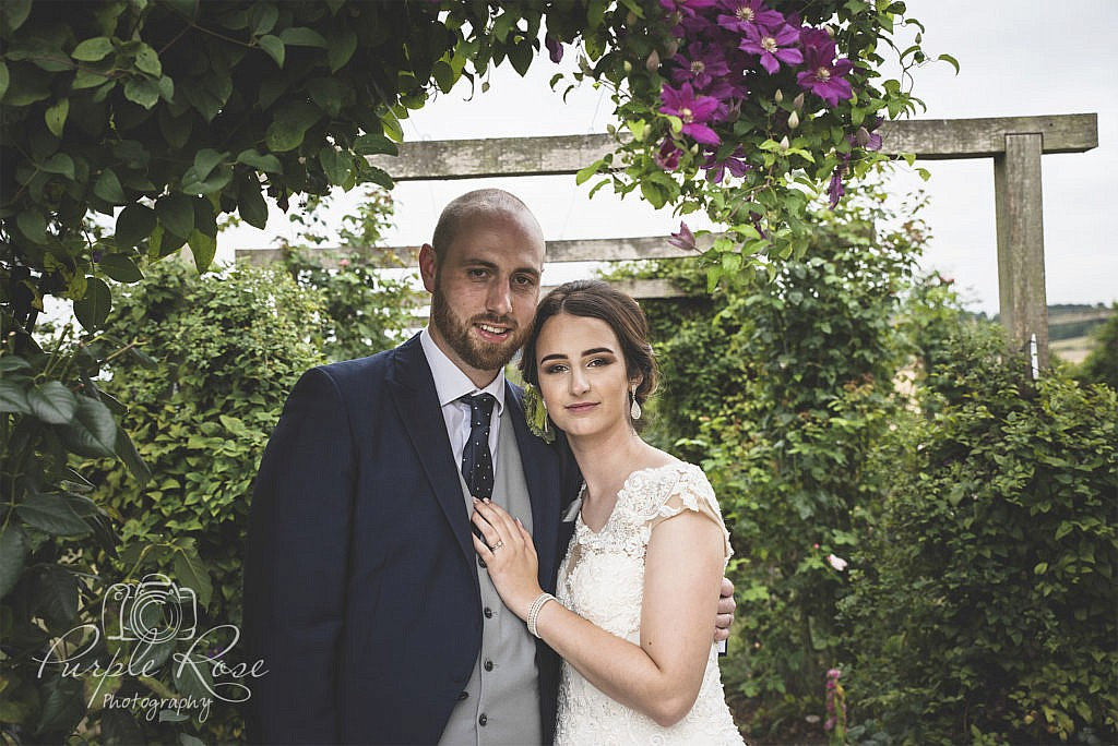 Bride and groom in a flower covered archway
